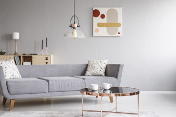 Lamp above grey settee with cushions in bright living room interior with poster and table. Real photo