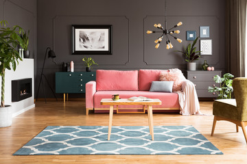 Wooden table on blue carpet in grey living room interior with fireplace and pink sofa. Real photo