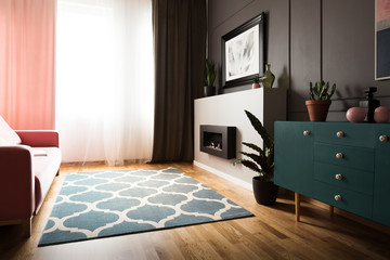 Plant on green cabinet in bright living room interior with fireplace and patterned carpet. Real photo