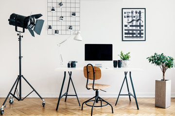 Desk and chair between plant and lamp in white freelancer's interior with posters. Real photo