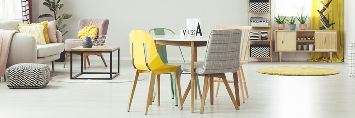 Yellow and grey chair at dining table in apartment interior with pouf next to sofa. Real photo