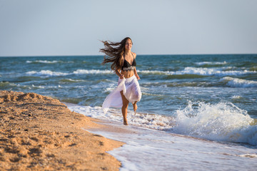 Beautiful girl running on the morning surf