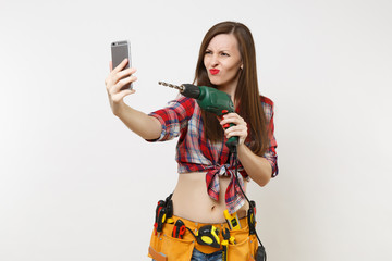 Strong excited handyman woman in shirt, kit tools belt full of instruments doing selfie on mobile phone with power electric drill isolated on white background. Female in male work. Renovation concept.