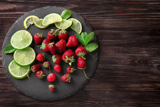 Ripe red strawberries with lime slices on slate plate