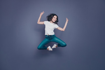 Crazy adorable pretty stylish trendy nice lovely cheerful curly-haired brunette girl in casual white t-shirt and jeans, fooling, flying in air, showing double v-sign, isolated on grey background