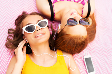 summer fashion, leisure and technology concept - smiling teenage girls in sunglasses and earphones lying on picnic blanket and listening to music from smartphone