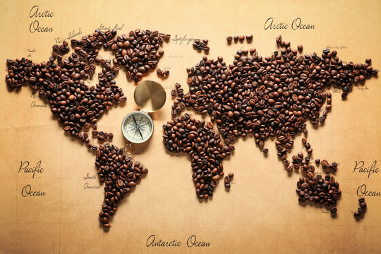 World map made of roasted coffee beans with compass, top view