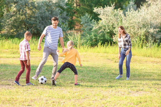 Family playing football in park on summer day