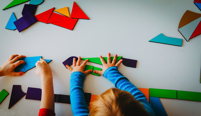 kids playing with puzzle or tangram, education concept
