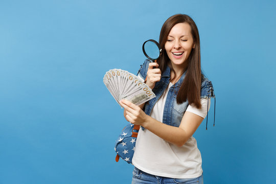 Young curious woman student with backpack look on bundle lots of dollars, cash money with magnifying glass check banknotes isolated on blue background. Verification for authenticity of money concept.