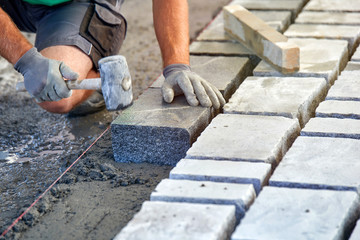 A workman's gloved hands use a hammer to place stone pavers. Worker creating pavement using cobblestone blocks and granite stones. Fototapete