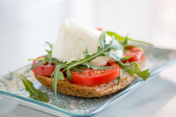 Italian style toast with light bread, arugula, tomato and mozzarella cheese