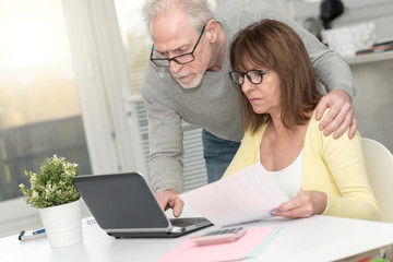 Senior couple checking financial document