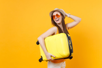 Traveler tourist woman in summer casual clothes, hat with suitcase isolated on yellow orange background. Female passenger traveling abroad to travel on weekends getaway. Air flight journey concept.