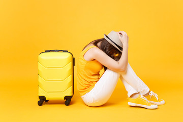 Sad traveler tourist woman in summer casual clothes, hat sit near suitcase isolated on yellow orange background. Female passenger traveling abroad to travel on weekends getaway. Air flight concept.