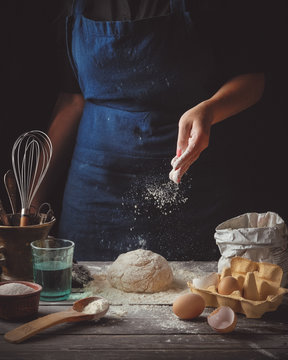 A young woman cooking homemade dough on a dark wooden rustic table. Toned image.