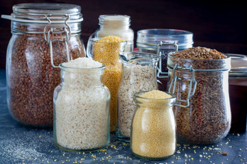 Various cereals in glass jars on a table, horizontal