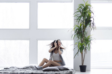 Young girl woman female adult wearing grey pajamas white top and socks sitting on blanket near the large windows, relaxing and listening to music in the light interior room with plant. Morning concept