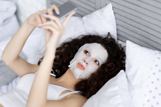 Brunette cute young girl female woman lying in bed with refreshing spa body care mask doing selfie in light room at home. Morning wake up / body care concept