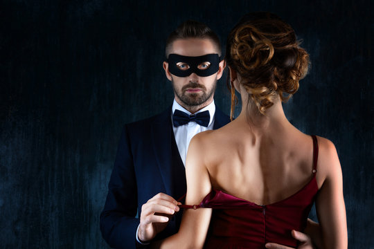 Rich millionaire man male in black carnaval mask bow tie and suit seduces tempts lures woman female in expensive red evening dress. Sex, tempts, harassment, sexism, seduction, henpecked issues