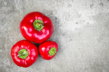 Ripe red peppers on grey concrete background