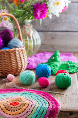 Multi-colored balls of cotton thread for crocheting in a wicker basket on a wooden table and ready knitted napkin made of multi-colored thread, selective focus
