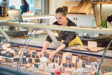 Verkäuferin sortiert Käse in Theke im Supermarkt ein