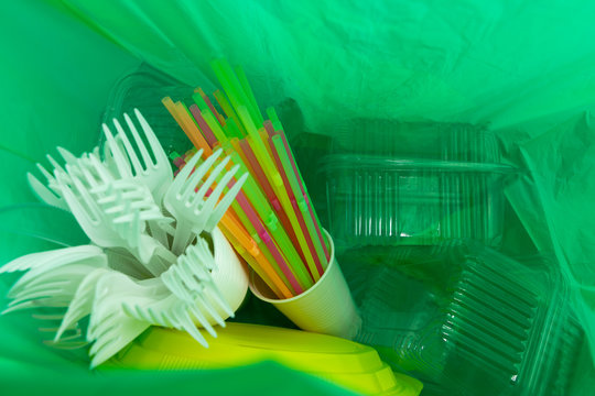 Inside of green plastic bag with single use cutlery and packages.