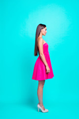 Profile side full body vertical view of serious brunette girl, lady in mini pink dress and high heels shoes, standing straight. Isolated over bright vivid turquoise background