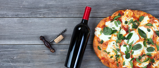 Freshly cooked homemade tomato and cheese pizza and red wine ready to serve