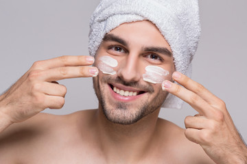 Cheerful man applying moizturizer on his face