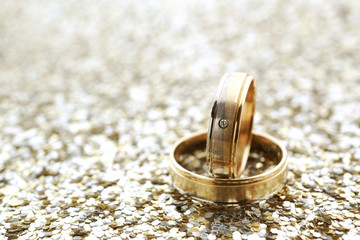 Gold wedding rings on glitter background with copy space