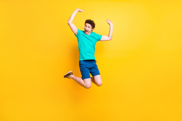 Full size length body picture of handsome curly-haired playful young guy wearing casual green t-shirt, shorts, shoes, jumping in air, hands up, party time. Isolated over yellow background