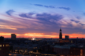 Hamburg at sunset scene with Dancing Towers, Ferris Wheel of Hamburg's Dom and St. Michael's church in a distant