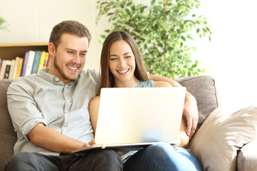 Happy couple using a laptop on a couch at home