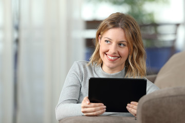 Woman thinking holding a tablet at home