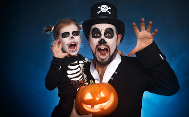 family father and daughter in costumes and make-up to Halloween with pumpkin