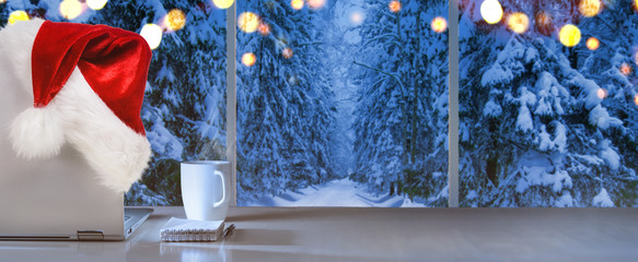 Laptop on table with Santa Claus hat at home with panoramic view through window of snowy trees in winter forest