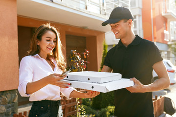 Pizza Delivery. Courier Giving Woman Boxes With Food Outdoors