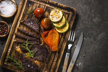 Grilled beef steak with vegetables top view.