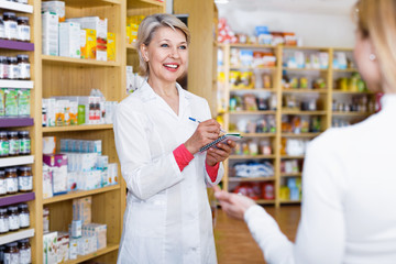 Mature female seller suggesting care products to young customer