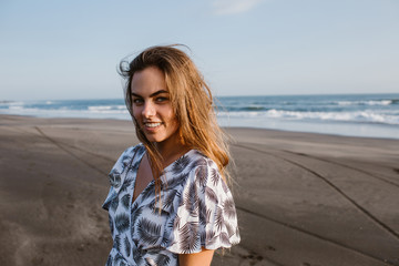 attractive girl standing in dress on beach in bali, indonesia and looking at camera