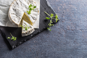 Cheese camambert from oregano herbs on slate board
