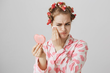 Gloomy bothered girl in pyjamas, wearing hair-curlers and holding heart-shaped mirror, wiping off makeup or mascara, being bothered or upset. Woman was crying over TV drama and now has bags under eyes