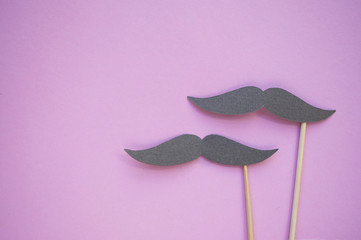 Photo booth props - moustaches on pink background with copyspace. Party and wedding set.