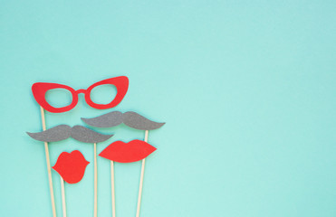 Colorful photo booth props glasses, lips and moustaches on blue background with copyspace.