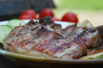 Grilled juicy pork chops with fresh tomato and cucumber salad