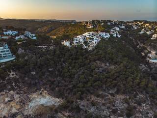 Summer 2018, Xabia, Province of Alicante, Valencia, Spain, Playa de la Granadella. Small spanish white houses on the hill surrounded and shaped by pines. Panoramic aerial photo from drone.