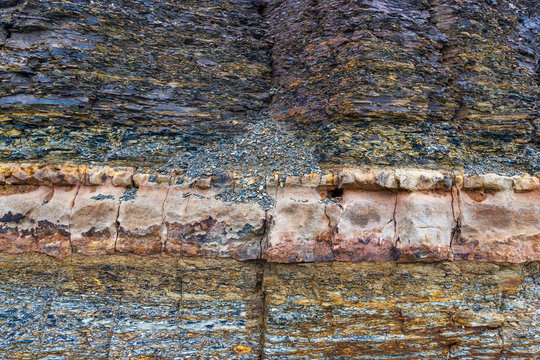 The vertical natural cliff with solid sedimentary layer and breccia