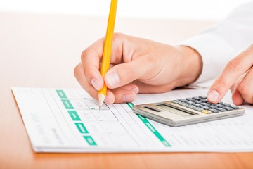 Close-up of a Businessman Using Calculator with Financial